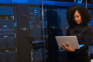 Woman on computer standing next to large computer servers