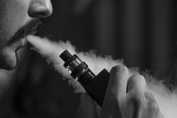 Image of man with moustache blowing vapour out of his mouth whilst holding a vape pen