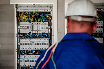 electrician in hard hat facing away from us in front of an electrical panel