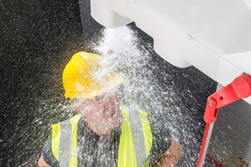 Employee standing under activated safety shower with hard hat and high-vis vest