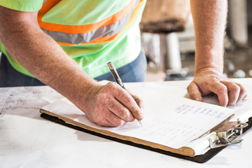 Worker in high vis writing on a clipboard