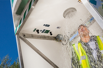 Male worker in high vis under an activated emergency tank shower
